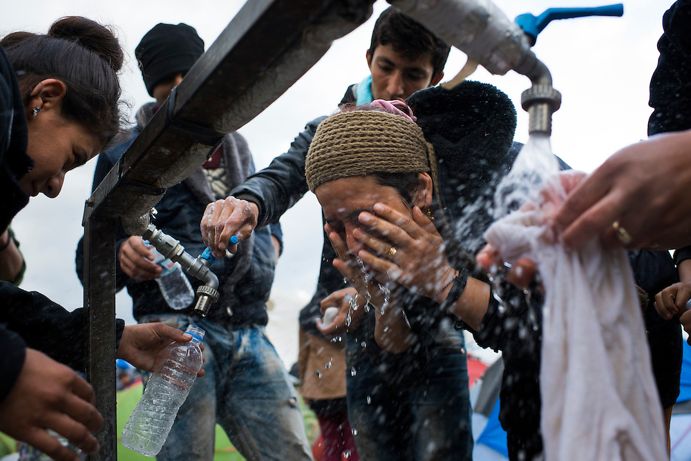 Jebila, a Yazidi woman from Iraq, center, washes her face at a refugee camp on the Macedonian (FYROM) border on March 7, 2016 in Idomeni, Greece.
