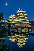 """As seen by the castle's red bridge at night, the Moon rises over Matsumoto Castle, which was built 1592-1614 in Matsumoto, Nagano Prefecture, Japan. Matsumoto Castle is a """"hirajiro"""" - a castle built on plains rather than on a hill or mountain, in Matsumoto. Matsumotojo's main castle keep and its smaller, second donjon were built from 1592 to 1614, well-fortified as peace was not yet fully achieved at the time. In 1635, when military threats had ceased, a third, barely defended turret and another for moon viewing were added to the castle. Interesting features of the castle include steep wooden stairs, openings to drop stones onto invaders, openings for archers, as well as an observation deck at the top, sixth floor of the main keep with views over the Matsumoto city."""