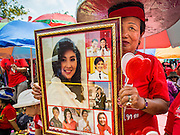 06 APRIL 2014 - BANGKOK, THAILAND:  A Red Shirt supporter holds up pictures of Yingluck Shinawatra, the embattled Thai Prime Minister during a rally in the Bangkok suburbs Sunday. Red Shirts and supporters of the government of Yingluck Shinawatra, the Prime Minister of Thailand, gathered in a suburb of Bangkok this weekend to show support for the government. The Thai government is dealing with ongoing protests led by anti-government activists. Legal challenges filed by critics of the government could bring the government down as soon as the end of April. The Red Shirt rally this weekend was to show support for the government, which public opinion polls show still has the support of most of the electorate.  PHOTO BY JACK KURTZ