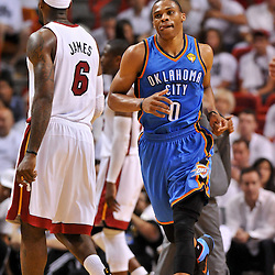 Jun 17, 2012; Miam, FL, USA; Oklahoma City Thunder point guard Russell Westbrook (0) runs past Miami Heat small forward LeBron James (6) during the third quarter in game three in the 2012 NBA Finals at the American Airlines Arena. Mandatory Credit: Derick E. Hingle-US PRESSWIRE