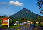 School Bus On The Road In The Tourist Town Of La Fortuna, Costa Rica, And Its Number One Tourist Attraction, the Arenal Volcano, Dominates The Background.