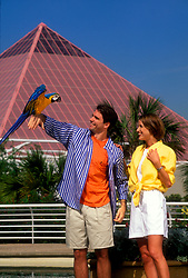 Man standing beside his wife and holding a parrot at Moody Gardens in Galveston