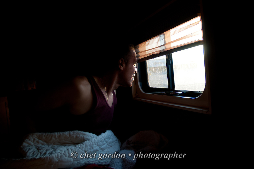 Over the road driver Jose Williams peers out of his sleeper compartment in Cambridge, PA on Sunday morning, May 3, 2015. Williams, a cross country trucker with a national household moving company, made the first of two delivery stops on the East Coast the following day with loads that originated in California's Bay Area the week of April 27th.  © Chet Gordon/THE IMAGE WORKS