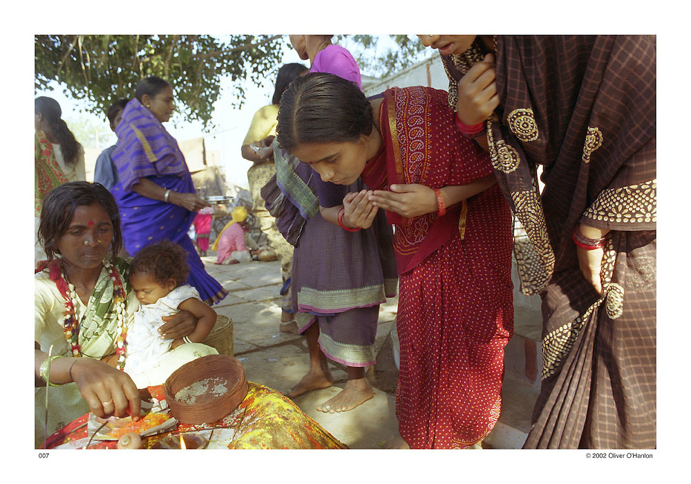 """India. Andhra Pradesh. Mahabubnagar District. 2002. Young Dalit women pray at a stump outside of a temple during a Hindu festival celebrating the goddess Yellamma. Because of their """"unthouchabe"""" status; caste Hindus refuse to let them into temples. The caste Hindus who still practice untouchability believe by letting Dalits into their temple it will become polluted; when this does occur, caste Hindus """"purify"""" the temple by cleaning the entire temple with coconut milk."""