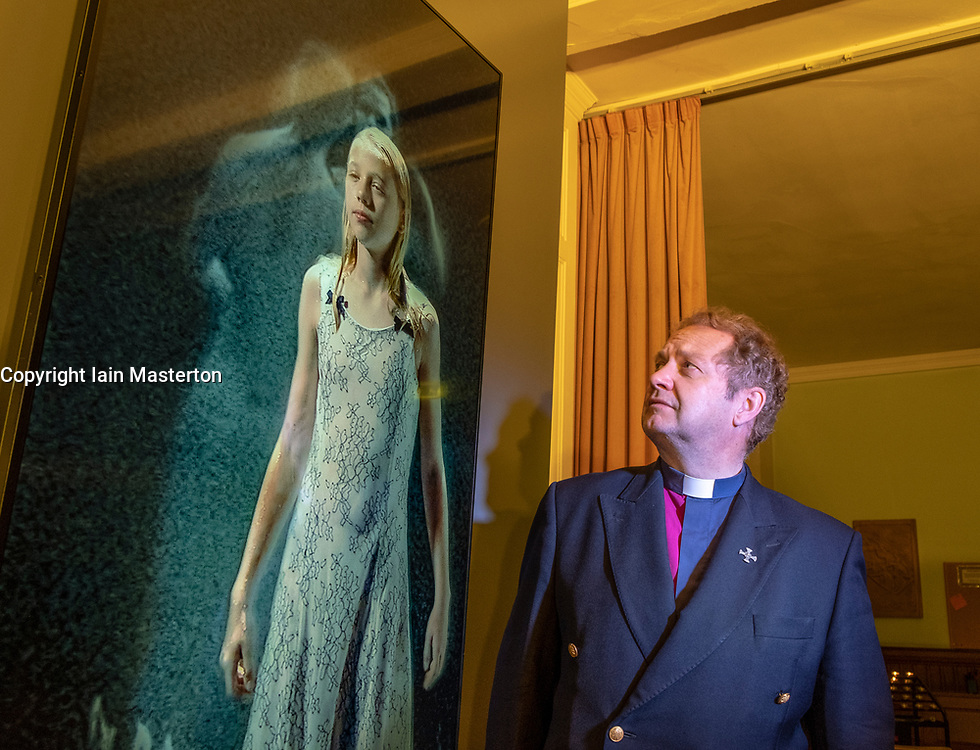 """22 May, 2018. Edinburgh, Scotland, UK. Video installation """"Three Women"""" by Bill Viola at St. Cuthbert's Parish Church in Edinburgh. The Minister of St. Cuthbert's, the Rev Peter Sutton, admires the work of Bill Viola which is on loan to the church until September. Although on display since 1 May, the display has not been publicised until this week."""