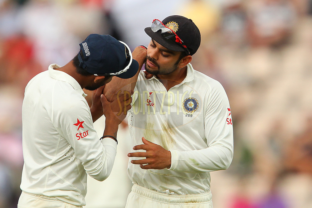 Virat Kohli of India examines his injured elbow during day two of the third Investec Test Match between England and India held at The Ageas Bowl cricket ground in Southampton, England on the 28th July 2014<br /> <br /> Photo by Ron Gaunt / SPORTZPICS/ BCCI