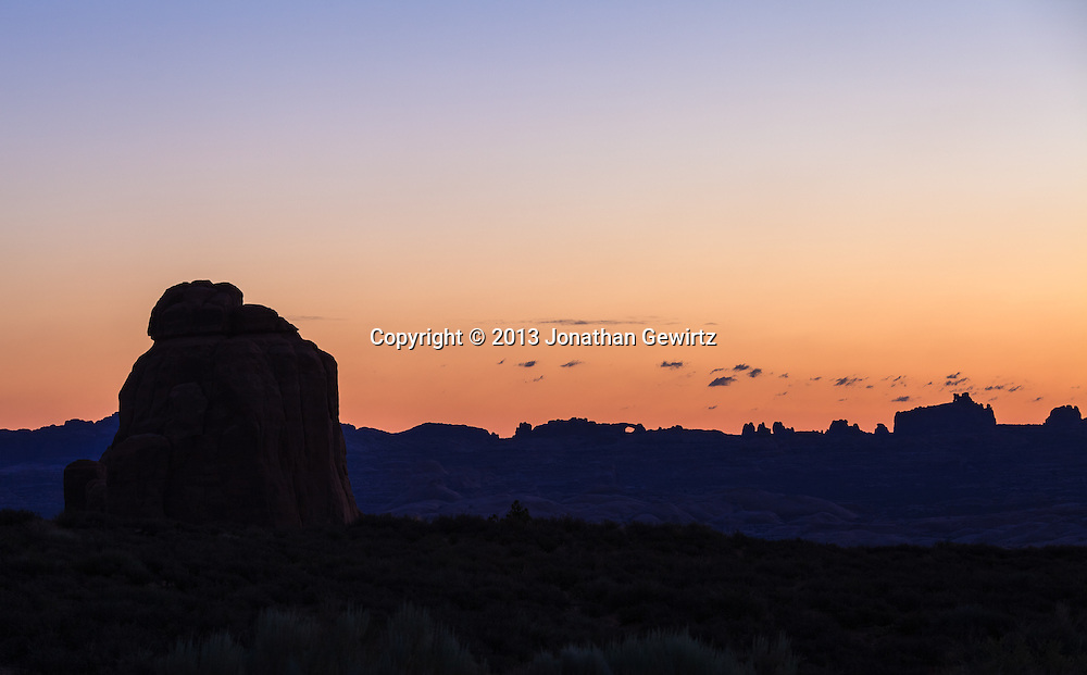 Light from the rising sun silhouettes striking rock formations in Arches National Park, Utah. WATERMARKS WILL NOT APPEAR ON PRINTS OR LICENSED IMAGES.