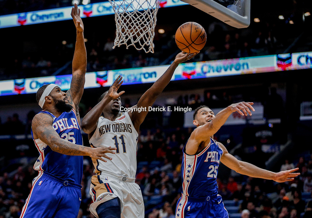 Dec 10, 2017; New Orleans, LA, USA; New Orleans Pelicans guard Jrue Holiday (11) shoots as Philadelphia 76ers forward Trevor Booker (35) and guard Ben Simmons (25) defend during the first quarter of a game at the Smoothie King Center. Mandatory Credit: Derick E. Hingle-USA TODAY Sports