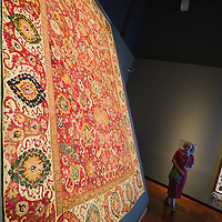 VENICE, ITALY - JUNE 16: A woman walks infront of  a mid sixteen century Persian rug on June 16, 2011 in Venice, Italy.Penelope's Labour: Weaving Words and Images, is an exhibition of antique and contemporary tapestries and carpets, curated by Adam Lowe and Jerry Brotton and will stay open until September 18.