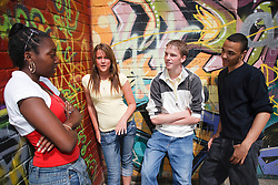 Teenage group standing by mural.