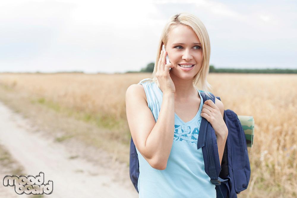Beautiful female hiker using mobile phone on field