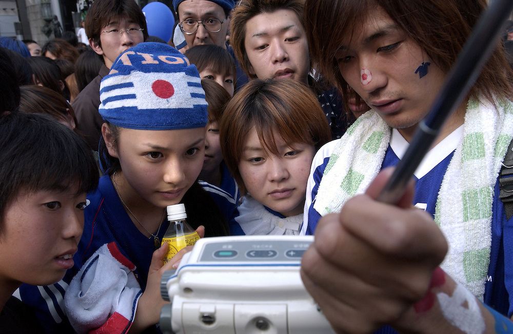 Young Japanese football supporters listen to the Japan vs Turkey match on portable television sets on the Ebisu-bashi bridge in the Minami area of Osaka...©David Dare Parker/AsiaWorks Photography