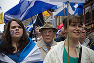 An elderly man and two women waving flags waiting on the Royal Mile for the start of a pro-Independence march and rally in the Scottish capital. The event, which was staged in support of the pro-Independence movement, was attended by an estimated by approximately 30,000 people. The referendum to decide whether Scotland will become an independent nation will be staged on 18th September 2014.