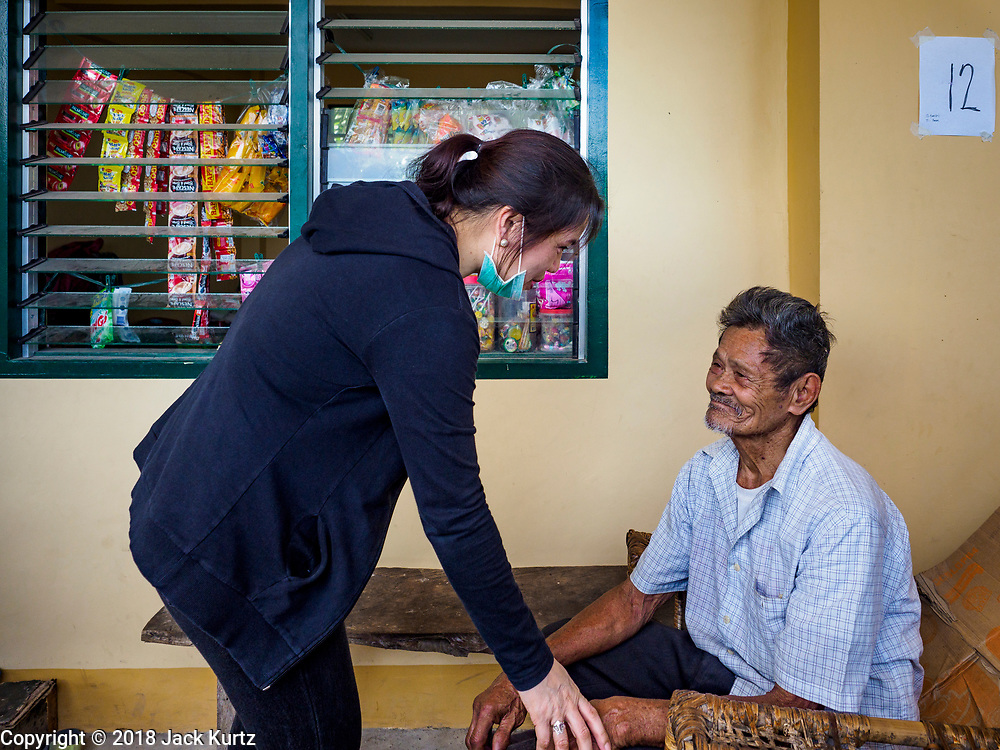 24 JANUARY 2018 - LIGAO, ALBAY, PHILIPPINES:  JUDITH WANASEN, a social worker managing a Ligao evacuee center, talks to IGNACIO CASIM, 84 years old. The Mayon volcano continued to erupt Tuesday night and Wednesday forcing the Albay provincial government to order more evacuations. By Wednesday evening (Philippine time) more than 60,000 people had been evacuated from communities around the volcano to shelters outside of the 8 kilometer danger zone. Additionally, ash falls continued to disrupt life beyond the danger zones. Several airports in the region, including the airport in Legazpi, the busiest airport in the region, are closed indefinitely because of the amount of ash the volcano has thrown into the air.   PHOTO BY JACK KURTZ