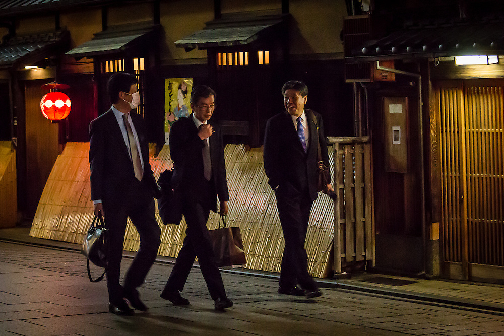 Three japanese colleagues relax after work with a stroll through Hanami Koji, in the Gion district of Kyoto