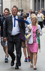 © Licensed to London News Pictures. 22/07/2015. London, UK. People struggle with high winds near 20 Fenchurch Street, also known as 'The Walkie Talkie' building, allegedly because of a downdraught effect caused by the design of the building.  Photo credit : James Gourley/LNP