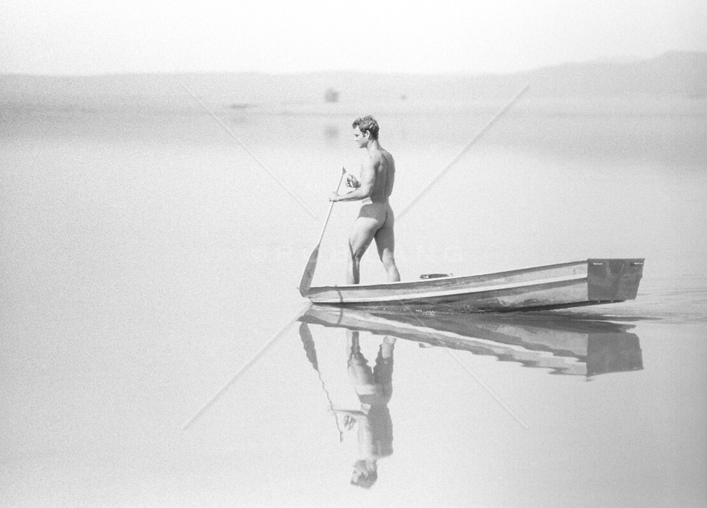 naked man standing in a rowboat on a lake in New Mexico