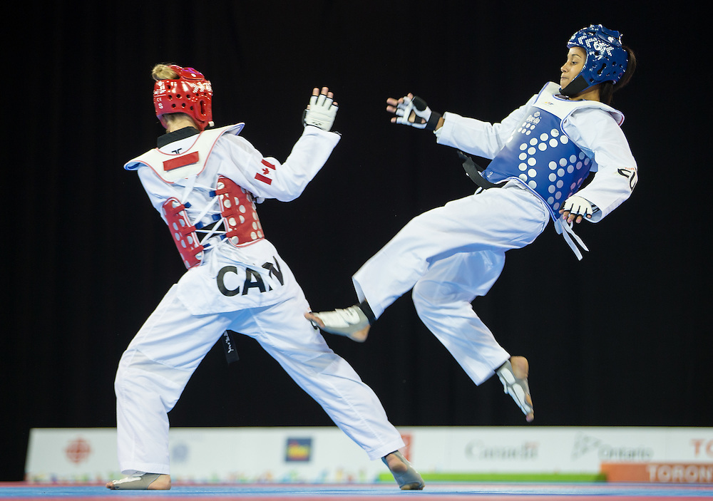 Yamicel Nunez (R) of Cuba kicks Evelyn Gonda of Canada during their bronze medal contest in the women's Taekwondo -57kg division of at the 2015 Pan American Games in Toronto, Canada, July 20,  2015.  AFP PHOTO/GEOFF ROBINS