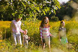 A woman and her three kids walk in a field at the Pell Farm in Grafton, Massachusetts.