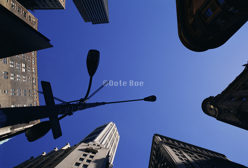 New York City buildings street lamp and signs silhouetted against blue sky