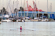 Young woman from the Vancouver Rowing Club rowing in Coal Harbour.  Photographed from the Stanley Park seawall along the western end of Coal Harbour in Vancouver, British Columbia, Canada