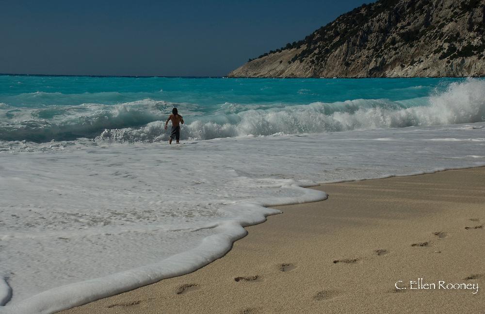 A man in heavy surf at Myrtos Beach, Kefalonia, the Ionian Islands, Greece