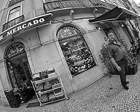 Market Vendor. Street Photography in Lisbon. Image taken with a Nikon D850 camera and 8-15 mm fisheye lens.
