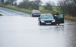 © Licensed to London News Pictures. 25/11/2012..North East England..A man is helped from his stranded car by his daughter as they became stuck in deep water near to Staithes in North Yorkshire this morning following heavy overnight rain that caused traffic disruption and flooding in parts of Cleveland and North Yorkshire...Photo credit : Ian Forsyth/LNP