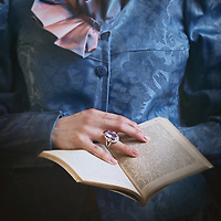 A closeup of a victorian woman, wearing a blue outfit, holding a book and touching it with one hand in a delicate manner.