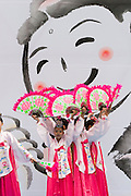 The annual Lotus Lantern Festival is held to celebrate Buddha's Birthday. Traditional fan dancers on stage in front of Buddha image.