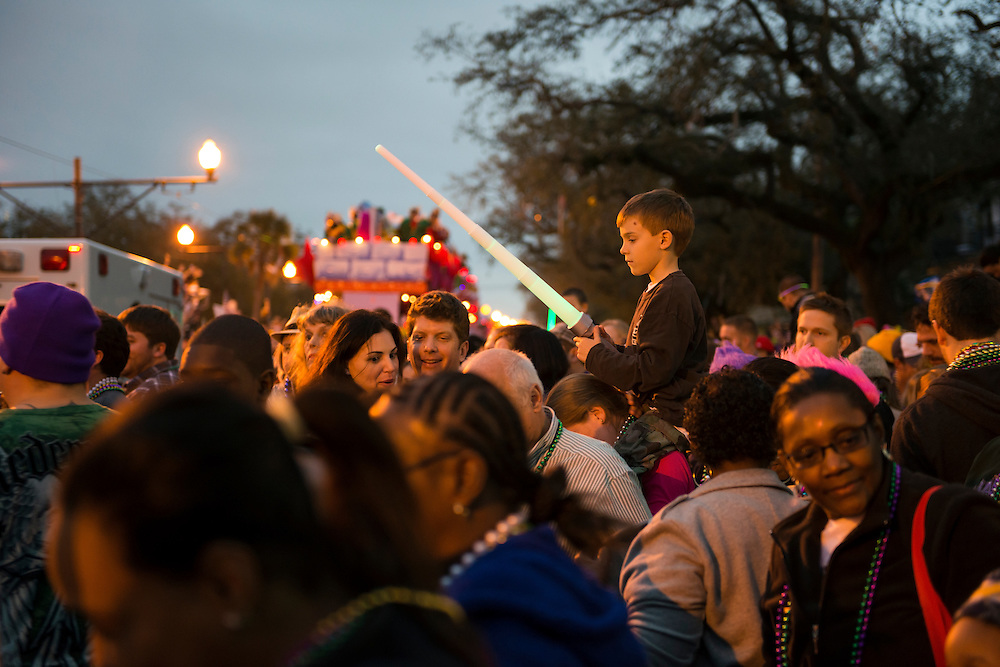 A young boy sits on a woman's shoulders during the Krewe of Endymion parade on Canal Street, holding an illuminated sword he was given by a passing float (background). While Mardi Gras is often associated with adult-themed wildness, it is also in many areas (such as the parades) a family-friendly event.