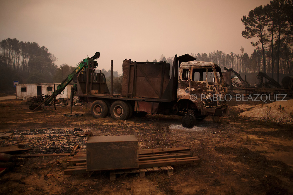 LEIRIA, PORTUGAL - JUNE 18:  A burned lorry stands near a road after a wildfire took dozens of lives on June 18, 2017 near Castanheira de Pera, in Leiria district, Portugal. On Saturday night, a forest fire became uncontrollable in the Leiria district, killing at least 62 people and leaving many injured. Some of the victims died inside their cars as they tried to flee the area.  (Photo by Pablo Blazquez Dominguez/Getty Images)