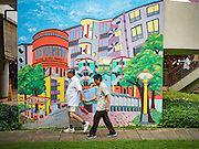 "27 DECEMBER 2016 - SINGAPORE: Shoppers walk past a mural in the Tiong Bahru Market. Tiong Bahru Market in Singapore is popular with local people who live in the community and expatriots living in Singapore. Market vendors sell a lot of imported foodstuffs and the food ""hawker"" area is one of the most popular in the city.      PHOTO BY JACK KURTZ"