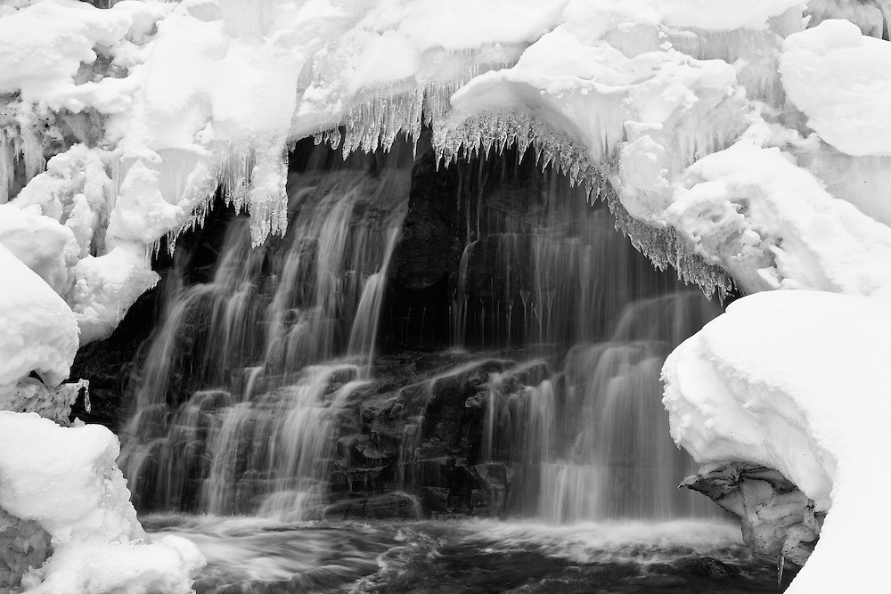 The South Fork of Eagle River flows through an opening in the snow and ice covering the waterfall in Chugach State Park, Eagle River in Southcentral Alaska. Winter. Afternoon.