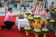 26 NOVEMBER 2012 - BANGKOK, THAILAND: A man wearing pink makes an offering of  a gift for the hospitalized King of Thailand at Siriraj Hospital in Bangkok. He was wearing pink because it's viewed as a fortuitous color that could bring the King better health. Siriraj was the first hospital in Thailand and was founded by King Chulalongkorn in 1888. It is named after the king's 18-month old son, Prince Siriraj Kakuttaphan, who had died from dysentery a year before the opening of the hospital. It's reported to one of the best hospitals in Thailand and has been home to Bhumibol Adulyadej, the King of Thailand, since 2009, when he was hospitalized to treat several ailments. Since his hospitalization tens of thousands of people have come to pay respects and offer get well wishes. The King's 85th birthday is on Dec 5 and crowds at the hospital are growing as his birthday approaches. The King is much revered throughout Thailand and is seen as unifying force in the politically fractured country.        PHOTO BY JACK KURTZ