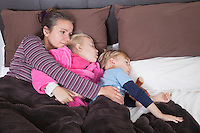 Mother lying in bed with two children