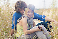 Smiling woman sitting with loving man in field