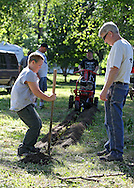 Tony Scolaro (from left), 12, and Pat Welsh both of Cedar Rapids work on digging a post hole for an electrical outlet at a campground near Bertram on Tuesday afternoon, May 29, 2012. (Stephen Mally/Freelance)