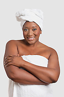 Portrait of woman with body and head wrapped in towels over white background