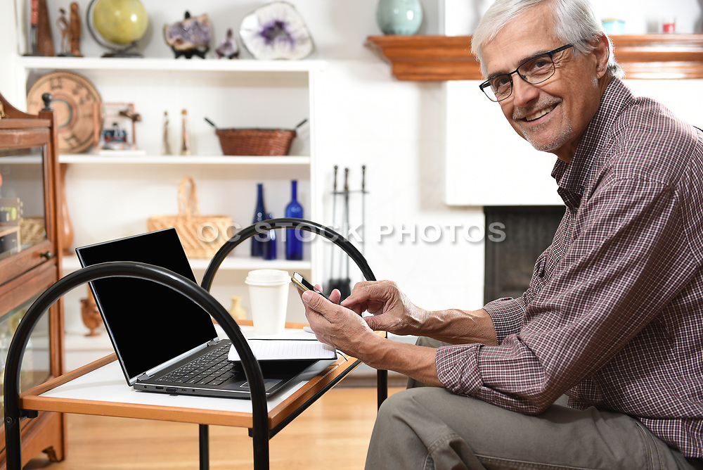Mature Adult Man Working From Home with His Laptop and Cell Phone