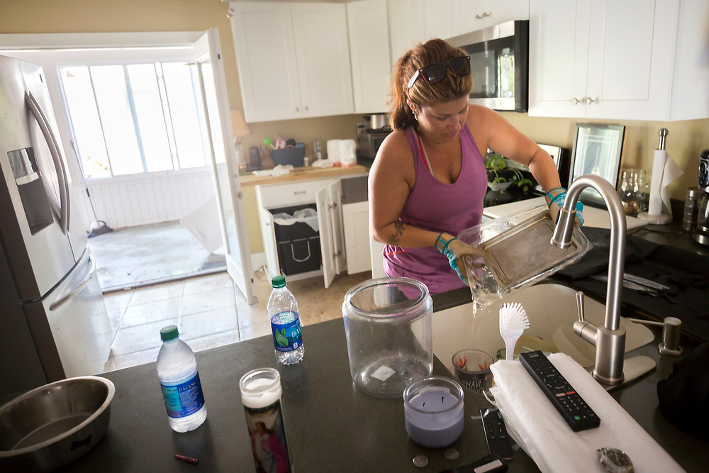 Cheryl M. Smith dumps water out of a pan filled with flood water, Tuesday, Sept., 12, 2017, on Tybee Island, Ga., after Tropical Storm Irma flooded her house with three feet of water. (AP Photo/Stephen B. Morton)