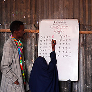 The Stars Foundation visiting Africa Educational Trust (AET) in Somaliland...Teacher Faysal teaching the children arithmetic's.  The school is made of corrugated steel and has to cater for many more children than it has room for. Faysal and his 2 fellow teachers work in shifts so that all children get a chance to receive some education...AET runs schools in camps for Internally Displaced People in and around Hargeisa. The camps go back to the civil war in 1991 and some of the inhabitants have been there 20 years.  Others are new-comers from the countryside fleeing climate change which is causing live stock die and crops to fail - ultimately leading to starvation.