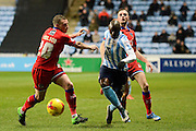 Coventry City striker Marc-Antoine Fortune skips past Oldham Athletic defender Brian Wilson during the Sky Bet League 1 match between Coventry City and Oldham Athletic at the Ricoh Arena, Coventry, England on 19 December 2015. Photo by Alan Franklin.