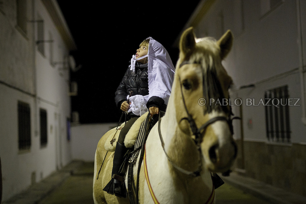 "A girl rides a horse during ""La Encamisa"" Festival on December 7,  2014 in Torrejoncillo, Extremadura region, Spain. ""La Encamisa"" is an ancient festival in honor of Immaculate Conception. Hundreds of horsemen wearing a white sheet gather outside the church in the main square. The procession starts when a banner with the image of Immaculate Conception is delivered to the horse rider steward and people cheer and shoot blanks. There are bonfires along the way where people gather to chat, eat traditional sweets and drink local wine. The origin of this tradition is unknown but it is believed the festival comes from a military event in which people from Torrejoncillo were involved. The war in Flanders in 1585, the Battle of Pavia or a legend of the siege suffered by city of Coria. (© Pablo Blazquez)"