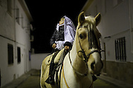 """A girl rides a horse during """"La Encamisa"""" Festival on December 7,  2014 in Torrejoncillo, Extremadura region, Spain. """"La Encamisa"""" is an ancient festival in honor of Immaculate Conception. Hundreds of horsemen wearing a white sheet gather outside the church in the main square. The procession starts when a banner with the image of Immaculate Conception is delivered to the horse rider steward and people cheer and shoot blanks. There are bonfires along the way where people gather to chat, eat traditional sweets and drink local wine. The origin of this tradition is unknown but it is believed the festival comes from a military event in which people from Torrejoncillo were involved. The war in Flanders in 1585, the Battle of Pavia or a legend of the siege suffered by city of Coria. (© Pablo Blazquez)"""