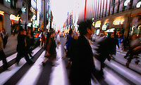Pedestrians cross the street at dusk in the Ginza district of Tokyo, Japan