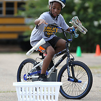 Brayden Holman, 9, drops his newspaper in the basket as part of the obstacle course for the CATCH Kids bike rodeo held Thursday at he Haven Acres Boys & Girls Club.