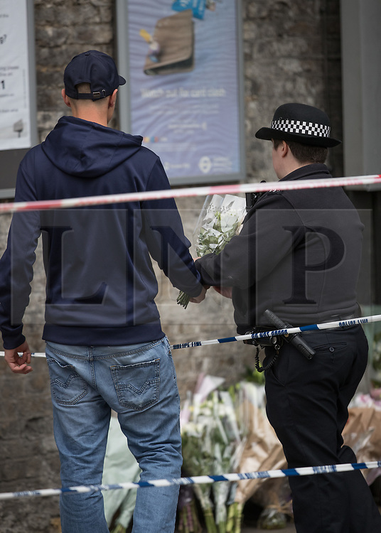 © Licensed to London News Pictures. 17/10/2017. London, UK. A man hands a floral tribute to a police officer near the crime scene. Police are investigating after a man in his 20's was stabbed to death and two others were injured in an incident on Monday night outside Parsons Green underground station a terrorist attack took place last month. Photo credit: Peter Macdiarmid/LNP