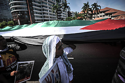 Image licensed to i-Images Picture Agency. 18/07/2014. Kuala Lumpur,Malaysia. Demonstrators hold a Palestine national flag as they protest against Israel's military action in Gaza during a demonstration in front of the US embassy in Kuala Lumpur on July 18, 2014.Picture by Mohd Firdaus / i-Images