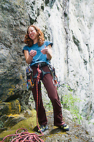 A late 20's woman wearing rock climbing gear laughs as she gets ready for a climb.